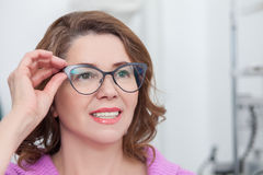 Cute lady is trying on eyewear in clinic Stock Images