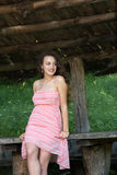 Cute lady wear a pretty summer dress. Leaning against a wooden kiosk table deep in the forest Stock Photos