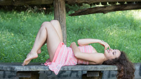 Cute lady wear a pretty summer dress. Lying on a wooden kiosk table deep in the forest, standing in profile, full length body ,horizontal photo Stock Image