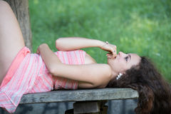 Cute lady wear a pretty summer dress. Lying on a wooden kiosk table deep in the forest, standing in profile ,horizontal photo Royalty Free Stock Photos