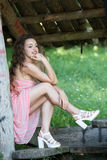 Cute lady wear a pretty summer dress. Sitting on a wooden kiosk in the forest, full length body ,vertical photo Royalty Free Stock Photography