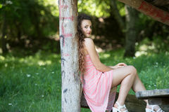 Cute lady wear a pretty summer dress. Sitting on a wooden kiosk in the forest, horizontal photo Royalty Free Stock Photo