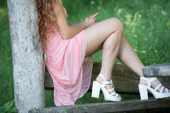 Cute lady wear a pretty summer dress. Sitting on a wooden kiosk in the forest, horizontal photo Stock Photo