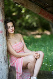 Cute lady wear a pretty summer dress. Sitting on a wooden kiosk in the forest, vertical photo Stock Image