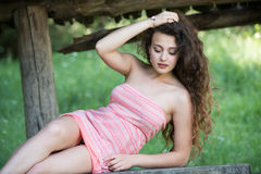 Cute lady wear a pretty summer dress. Sitting on a wooden kiosk table deep in the forest Royalty Free Stock Photos