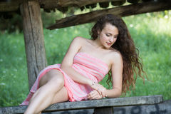 Cute lady wear a pretty summer dress. Sitting on a wooden kiosk table deep in the forest Royalty Free Stock Photography