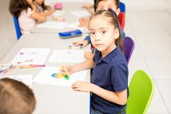Cute Latin girl coloring in a classroom. Pretty preschool Latin girl doing a coloring activity with crayons in a classroom and making eye contact Stock Images