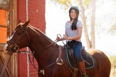 Cute Latin girl riding a horse Stock Photo