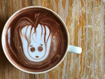 Cute Latte art coffee on the wooden table, latte art coffee shape look like `Groot` royalty free stock photography