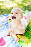 Cute laughing baby on a beach towel Royalty Free Stock Photography