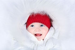 Cute laughing baby with blue eyes in snow suit. Cute laughing baby with beautiful blue eyes in a white snow suit Royalty Free Stock Images
