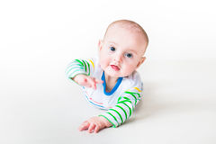 Cute laughing baby boy playing on his tummy. Happy laughing funny baby boy wearing a colorful shirt learning to crawl playing on his tummy, on white background Stock Photography