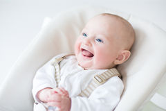 Cute laughing baby boy sitting in a high chair. Waiting for lunch Royalty Free Stock Photo