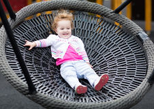Cute laughing baby girl on a net swing enjoying a sunny day royalty free stock image
