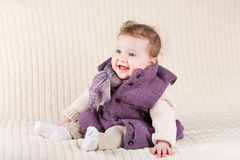 Cute laughing baby girl in purple jacket on knitted royalty free stock image