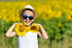 Cute laughing blond boy in sun glasses and hat with sunflowers on field outdoors Royalty Free Stock Images