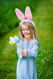 Cute laughing blond little girl wearing white rabbit ears. Cute laughing blond little girl wearing white and punk rabbit or bunny ears and blue knitted dress and Stock Image
