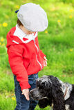 Cute laughing boy and his dog, playing in the park, springtime Royalty Free Stock Image