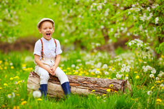 Cute laughing boy sitting on wooden stump in spring garden Stock Images