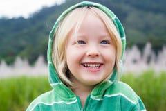 Cute laughing boy wearing hoodie in a field. Cute laughing child in a green hoodie, standing in a sugar cane field Stock Photo