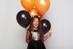 Cute laughing girl with candy and balloons