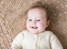 Cute laughing little baby on brown knitted blanket Royalty Free Stock Images