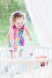 Cute laughing toddler girl with her newborn brother Stock Photos