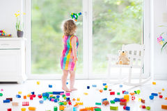 Cute laughing toddler girl playing with colorful blocks Royalty Free Stock Image