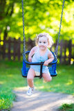 Cute laughing toddler girl swinging ride on playground. Happy laughing toddler girl with curly hair wearing a blue dress enjoying a swing ride on a sunny summer Royalty Free Stock Image