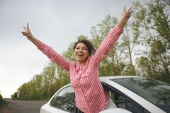 Cute laughing young woman hanging out her head from a car through the open window enjoying the freedom of the breeze in royalty free stock photography