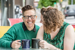 Cute lesbian couple joking outside at bistro stock images