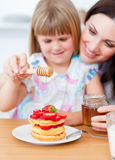 Cute lgirl and her mother putting honey on waffles stock image
