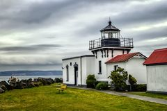 Cute lighthouse stands watch under a cloudy sky royalty free stock images