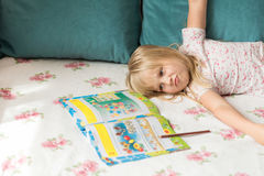 Cute liitle blonde girl lying on a bed and making homework in the workbook with a pencil Royalty Free Stock Photography