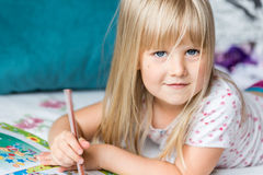 Cute liitle blonde girl lying on a bed and making homework Royalty Free Stock Images