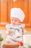 Cute liitle girl in chef`s hat sitting on the kitchen floor soil stock photography