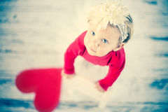 Cute liitle girl looking up. Cute liitle girl with paper heart Royalty Free Stock Image