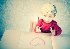 Cute liitle girl sketching a heart. On a white paper Royalty Free Stock Photo