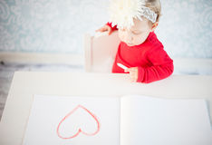 Cute liitle girl sketching a heart Royalty Free Stock Photography