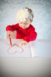 Cute liitle girl sketching a heart. On a white paper Stock Images