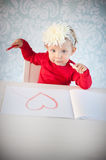 Cute liitle girl sketching a heart Royalty Free Stock Photos