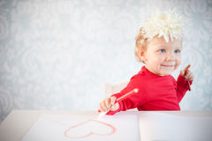 Cute liitle girl sketching a heart Royalty Free Stock Image