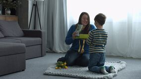Cute liitle son giving a gift to her happy mother. Excited smiling mother receiving a holiday gift box from her loved son on Mother`s Day in domestic room stock video