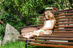 Cute litle barefoot girl sitting on the bench Royalty Free Stock Images