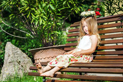 Cute litle barefoot girl sitting on the bench Royalty Free Stock Photo