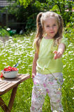 Cute litle girl with strawberries on a meadow full with flowers Royalty Free Stock Photo