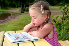 Cute Litle Girl With Newspaper Royalty Free Stock Images