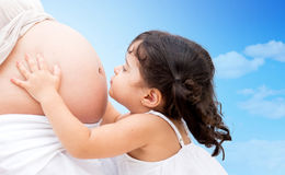 Girl kissing mums belly Royalty Free Stock Photography