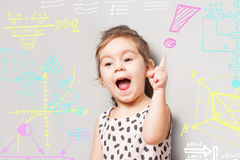 Cute litte girl who looks like found a solution and various quations and diagrams and graphics royalty free stock photography
