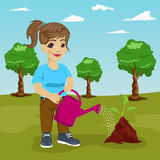 Cute littke girl watering a plant in park Royalty Free Stock Photo